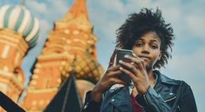Muchacha afro rizada con smartphone cerca de la catedral Fotografía de archivo libre de regalías