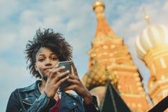 Muchacha afro rizada con smartphone en Plaza Roja Imagenes de archivo