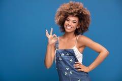 Muchacha afro sonriente que muestra símbolo aceptable Foto de archivo