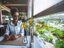 Muchacha afroamericana atractiva en café al lado de la ventana Foto de archivo libre de regalías