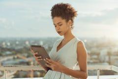 Muchacha afroamericana con la PC de la tableta al aire libre en el tejado Imágenes de archivo libres de regalías