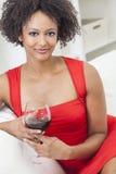 Muchacha afroamericana de la raza mixta que bebe el vino rojo Imagen de archivo