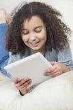 Muchacha afroamericana de la raza mixta que usa el ordenador de la tableta Fotografía de archivo