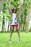 Muchacha afroamericana del adolescente con el salto extendido de las manos con la expresión positiva Fotos de archivo libres de regalías
