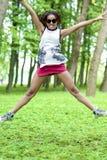 Muchacha afroamericana del adolescente con el salto extendido de las manos con la expresión positiva Imágenes de archivo libres de regalías