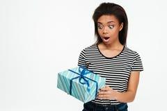 Muchacha afroamericana del adolescente que sostiene y que mira actualmente la caja Foto de archivo libre de regalías