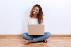 Muchacha afroamericana del estudiante que usa un ordenador portátil - el PE negro Imagenes de archivo