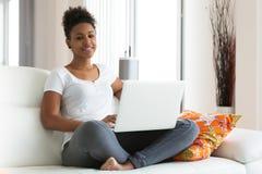Muchacha afroamericana del estudiante que usa un ordenador portátil - el PE negro Imagen de archivo