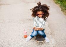 Muchacha afroamericana hermosa con smartphone y el monopatín Imágenes de archivo libres de regalías