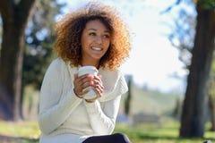Muchacha afroamericana joven con el peinado afro con la taza de café Imagenes de archivo