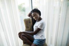 Muchacha afroamericana joven hermosa que se sienta en el sofá cerca de ventana en casa imagen de archivo libre de regalías