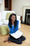 Muchacha afroamericana joven que lee un libro Foto de archivo libre de regalías