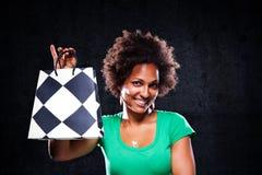Muchacha afroamericana linda con un bolso de compras Imagen de archivo libre de regalías