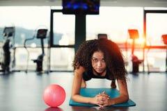 Muchacha afroamericana linda que hace ejercicio en una estera de la yoga Imagen de archivo libre de regalías