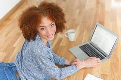 Muchacha afroamericana negra del estudiante que usa un ordenador portátil Fotografía de archivo libre de regalías