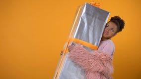 Muchacha afroamericana que lleva la caja de regalo grande, las ventas y las primas, entrega del día de fiesta almacen de video