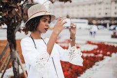 Muchacha afroamericana que toma las fotos en la calle vía el teléfono celular Fotografía de archivo