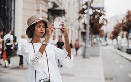 Muchacha afroamericana que toma las fotos en la calle vía el teléfono móvil Imagenes de archivo