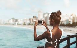 Muchacha afroamericana que toma las imágenes de la costa usando su cellpho Foto de archivo libre de regalías