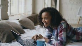 Muchacha afroamericana rizada lauging usando el ordenador portátil para compartir los medios sociales que mienten en cama en casa Imagen de archivo