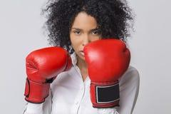 Muchacha afroamericana seria con los guantes de boxeo rojos que llevan para Foto de archivo libre de regalías