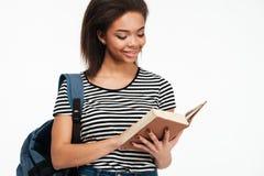 Muchacha afroamericana sonriente del adolescente con el libro de lectura de la mochila Fotografía de archivo