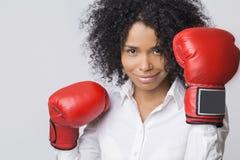 Muchacha afroamericana sonriente en guantes de boxeo rojos en el aire Fotos de archivo