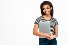 Muchacha afroamericana sonriente que celebra el ordenador portátil y la mirada de la cámara Foto de archivo libre de regalías