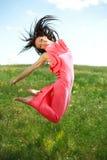 Muchacha agraciada de salto y que vuela en el fondo del cielo azul Imagen de archivo