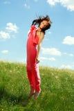 Muchacha agraciada de salto y que vuela en el fondo del cielo azul Imagenes de archivo