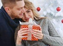 Muchacha agradable alegre en los brazos de un novio con los regalos de la Navidad fotografía de archivo libre de regalías