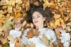 Muchacha agradable cubierta con las hojas otoñales Mujer joven que coloca en la tierra cubierta por el follaje de otoño en parque Foto de archivo libre de regalías