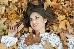 Muchacha agradable cubierta con las hojas otoñales Mujer joven que coloca en la tierra cubierta por el follaje de otoño en parque Imagen de archivo libre de regalías