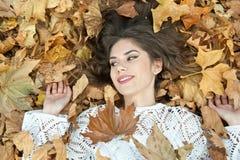 Muchacha agradable cubierta con las hojas otoñales Mujer joven que coloca en la tierra cubierta por el follaje de otoño en parque Fotos de archivo libres de regalías