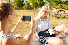 Muchacha agradable del adolescente que toma las fotos de su abuela en una comida campestre Foto de archivo libre de regalías