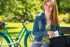 Muchacha agradable del estudiante que se sienta en el parque Fotografía de archivo libre de regalías