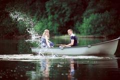 Muchacha agradable e individuo que salpican en el lago Foto de archivo libre de regalías