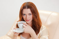 Muchacha agradable en bata casera beige con una taza de café Foto de archivo libre de regalías