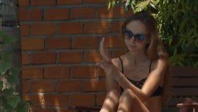 Muchacha agradable en brazos de las manchas de las gafas de sol con la protección solar