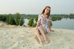 Muchacha agradable en la arena cerca del lago de la ciudad Imágenes de archivo libres de regalías