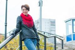 Muchacha agradable en la bufanda roja al aire libre imagen de archivo
