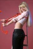 Muchacha agradable en pantalones vaqueros en un fondo rosado Imagen de archivo libre de regalías