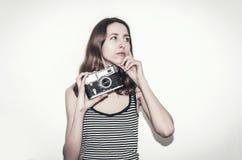Muchacha agradable en una camiseta rayada con una cámara del vintage en sus manos Fotografía de gente foto de archivo libre de regalías