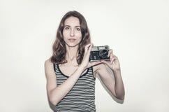 Muchacha agradable en una camiseta rayada con una cámara del vintage en sus manos Fotografía de gente imagen de archivo libre de regalías