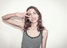 Muchacha agradable en una camiseta rayada Los fingeres gesticulan v imagenes de archivo