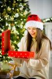 Muchacha agradable la abertura morena una caja con el regalo de Navidad Fotos de archivo