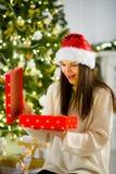 Muchacha agradable la abertura morena una caja con el regalo de Navidad Fotos de archivo libres de regalías