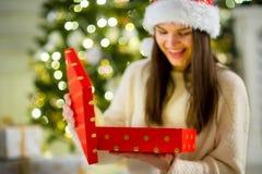 Muchacha agradable la abertura morena una caja con el regalo de Navidad Imagen de archivo libre de regalías