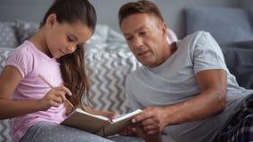 Muchacha agradable linda que descansa con su padre almacen de video