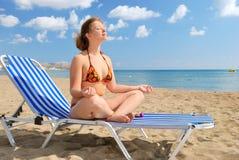 Muchacha agradable meditating en la playa Fotos de archivo